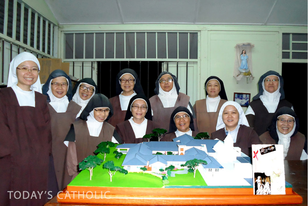 The Carmelite nuns posing with the model of their new Monastery